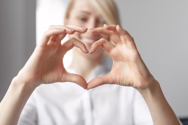 Giovane femmina che mostra un cuore a forma di con le sue mani