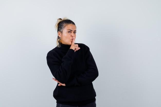 Giovane femmina che mostra il gesto di silenzio in maglione a collo alto nero e che sembra sicura. vista frontale.
