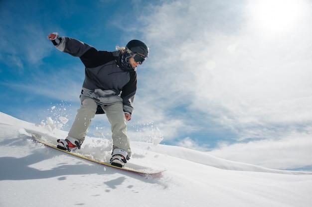 Giovane snowboarder femminile che corre giù per il pendio della montagna