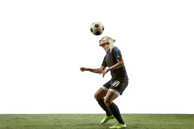 Giovane calciatore o calciatore femminile con capelli lunghi in abbigliamento sportivo e stivali che danno dei calci alla palla per l'obiettivo nel salto su fondo bianco. concetto di stile di vita sano, sport professionistico, movimento, movimento.