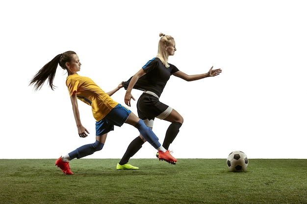 Giovani calciatori femminili di calcio o di calcio con capelli lunghi in abbigliamento sportivo e stivali che si allenano su sfondo bianco. concetto di stile di vita sano, sport professionistico, movimento, movimento. lotta per il gol.