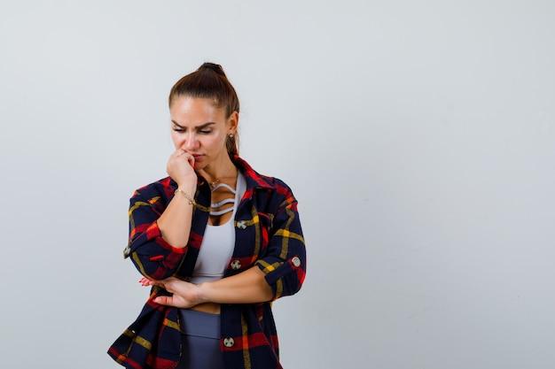 Giovane donna in piedi in posa di pensiero mentre guarda in basso in top corto, camicia a scacchi, pantaloni e guardando pensieroso, vista frontale.