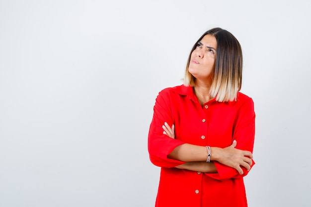 Giovane donna in piedi con le braccia incrociate mentre alza lo sguardo in una camicia rossa oversize e sembra premurosa, vista frontale.