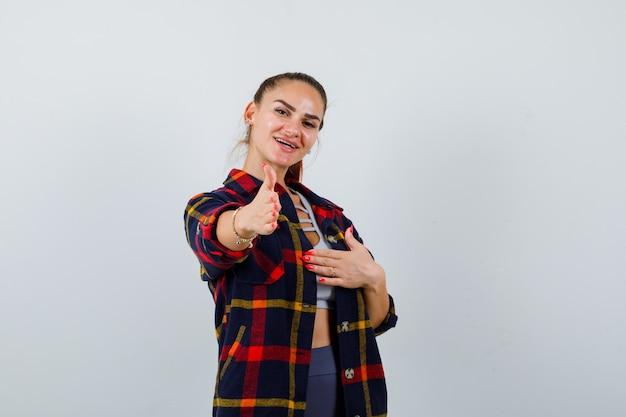 Giovane femmina che allunga la mano per salutare in crop top, camicia a scacchi e guardando felice, vista frontale.