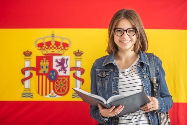 La giovane studentessa in vetri tiene il libro di testo aperto davanti alla bandiera della spagna.
