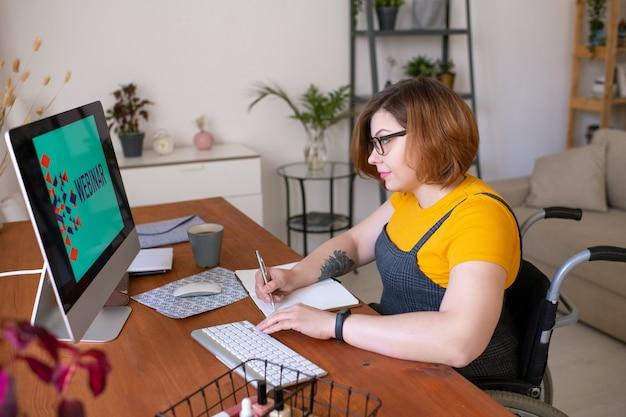 Giovane studentessa che prende appunti nel blocco note mentre era seduto davanti al monitor del computer a casa e guardando lo schermo durante il webinar