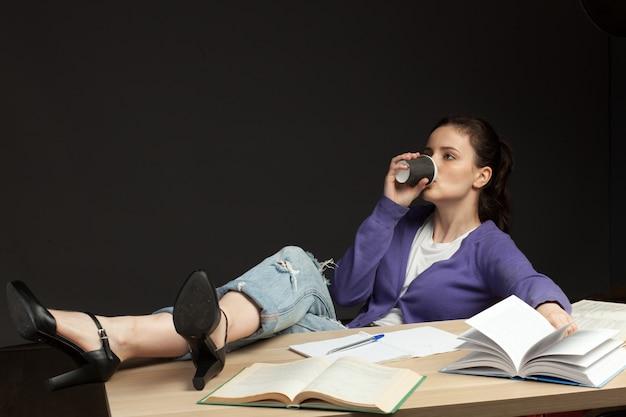 Negligenza della giovane studentessa all'istruzione, bere caffè isolato