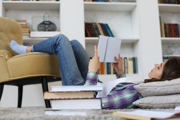 Giovane studentessa che studia a casa, si prepara per gli esami universitari, sdraiata sul pavimento contro l'accogliente interno domestico, circondata da una pila di libri.