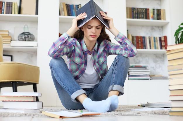 Giovane studentessa che studia a casa, si prepara per gli esami universitari, si preoccupa degli esami finali, si siede sul pavimento contro l'accogliente interno domestico, circondata da una pila di libri.