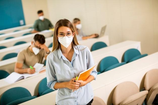 Giovane studentessa che indossa maschera medica protettiva per il viso per la protezione da virus in piedi in aula