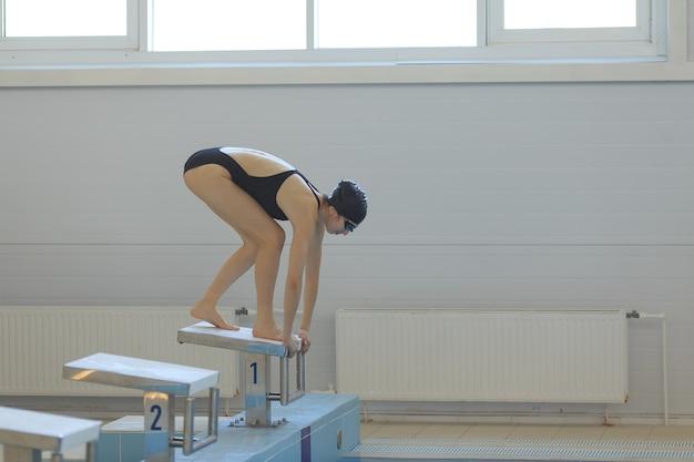 Giovane nuotatrice in posizione bassa sul blocco di partenza in una piscina.