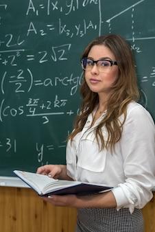 Giovane insegnante femminile nell'aula scolastica durante la lezione, vicino alla lavagna con formule matematiche scritte. formazione scolastica