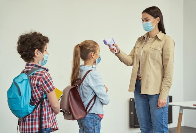 Giovane insegnante di sesso femminile che indossa una maschera protettiva per misurare la temperatura dei bambini con lo screening digitale