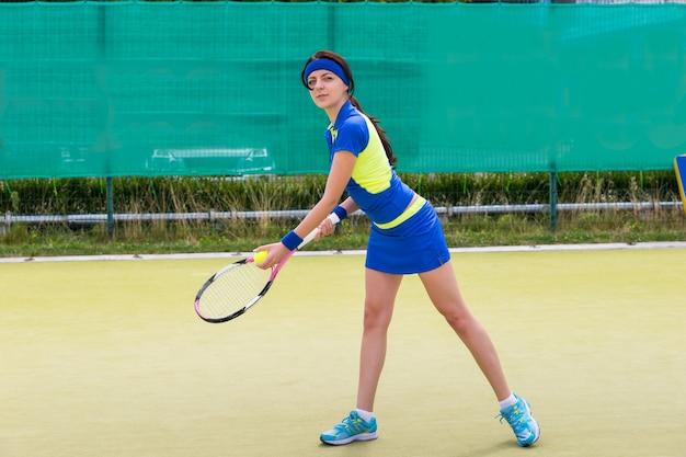 Giovane giocatore di tennis femminile che indossa un abbigliamento sportivo giocando a tennis su un campo all'aperto in estate