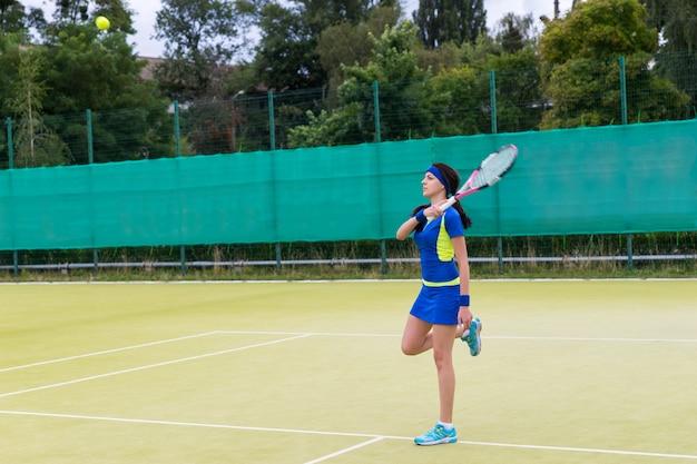 Giovane giocatore di tennis femminile che indossa un abbigliamento sportivo in fase di riscaldamento prima della partita di tennis su un campo all'aperto in estate o in primavera