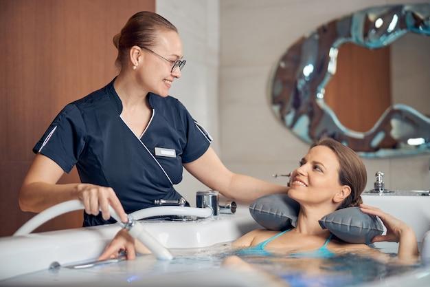 Giovane terapista femminile che sorride al suo paziente durante la procedura di idroterapia in un salone spa