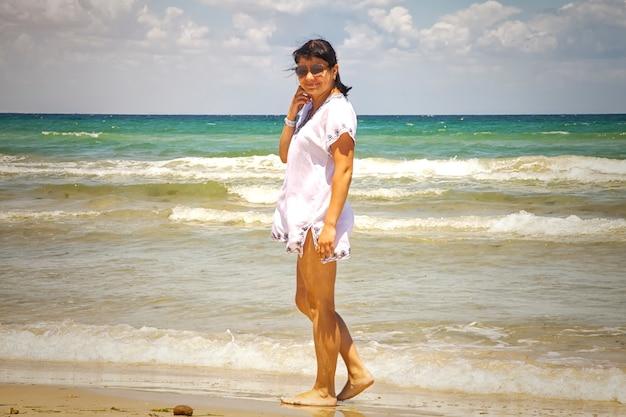 Giovane turista femminile in tunica e occhiali da sole sullo sfondo del mar mediterraneo, spiaggia sabbiosa. ragazza in vacanza. toni caldi diurni. signora che cammina sulla spiaggia, città di villeggiatura a tunisi, in africa, all'inizio della primavera