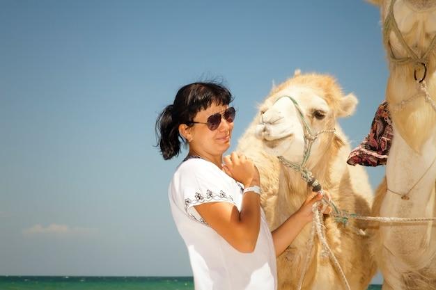 Giovane turista femminile in tunica e occhiali da sole posa con cammelli sullo sfondo mar mediterraneo, spiaggia sabbiosa. ragazza in vacanza. giocare con i cammelli. località turistica in tunisia, africa, all'inizio della primavera