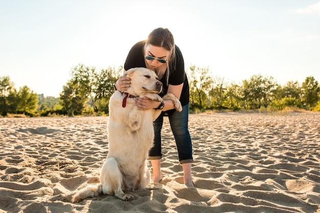 Giovane cane da riporto di labrador di addestramento femminile sulla spiaggia al tramonto