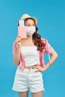 Giovane viaggiatrice che indossa una maschera facciale per proteggere il coronavirus