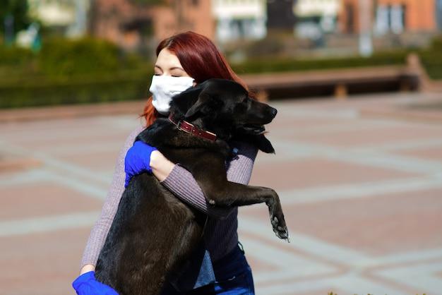 Giovane donna che usa una maschera facciale come prevenzione della diffusione del coronavirus che cammina con il suo cane. immagine del concetto di pandemia globale covid-19.