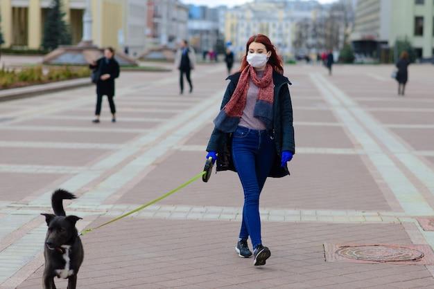 Giovane donna che usa una maschera facciale come prevenzione della diffusione del coronavirus che cammina con il suo cane