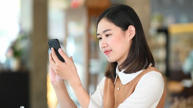 Giovane donna utilizzando il telefono cellulare navigando in internet presso la caffetteria.