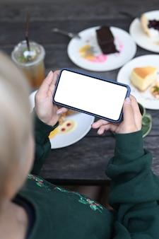 Giovane donna che utilizza smart phone per scattare foto di deliziosi pasticcini durante il riposo nella caffetteria.