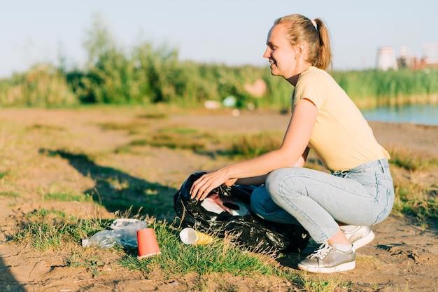 Giovane volontaria soddisfatta di aver raccolto spazzatura, bottiglie di plastica e tazze di caffè pulite
