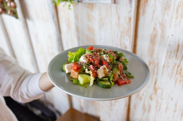 La giovane cameriera tiene tra le mani il piatto con l'insalata greca.