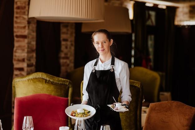 Giovane cameriere femminile in uniforme con guanti medicali che serve nel ristorante