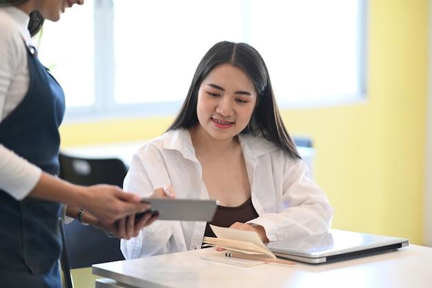 Giovane cameriere femminile utilizzando la tavoletta digitale.