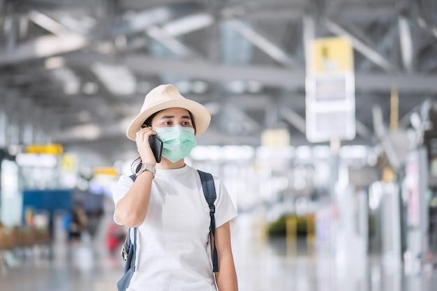 Giovane donna che indossa la maschera per il viso e utilizza lo smartphone mobile nel terminal dell'aeroporto, protezione dalla malattia da coronavirus (covid-19), donna asiatica viaggiatrice con cappello. nuovo concetto di bolla normale e di viaggio
