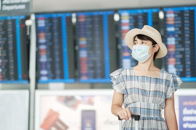 Giovane femmina che indossa la maschera per il viso con bagagli controllo tempo di volo in aeroporto