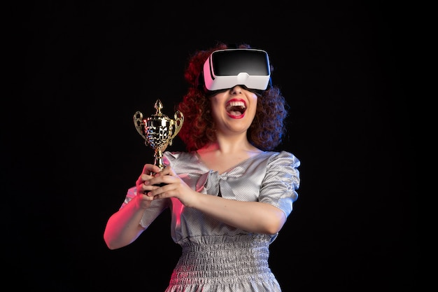 Giovane donna che indossa l'auricolare vr con la tazza su un gioco di visione di videogiochi scuro