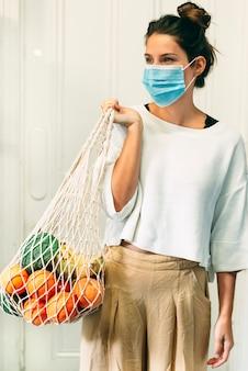Una giovane donna con una maschera e una borsa della spesa riutilizzabile in rete piena di frutta e verdura