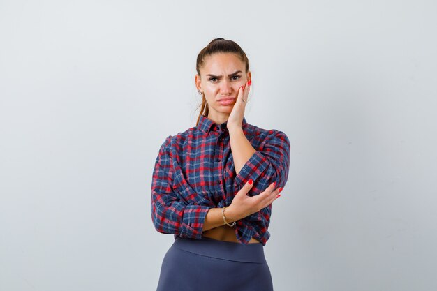 Giovane femmina con la mano sulla guancia in camicia a scacchi, pantaloni e guardando pensieroso. vista frontale.