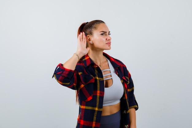 Giovane donna con la mano dietro l'orecchio in crop top, camicia a scacchi, pantaloni e sguardo curioso. vista frontale.