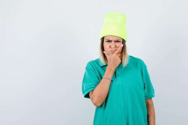 Giovane donna con la mano sul viso in t-shirt polo, berretto e annoiata. vista frontale.