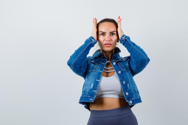 Giovane donna con le mani sulla testa in top corto, giacca, pantaloni e sguardo smemorato. vista frontale.