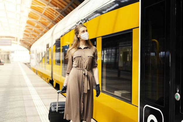 Giovane donna con una valigia che indossa guanti e una maschera facciale in una stazione ferroviaria - covid-19