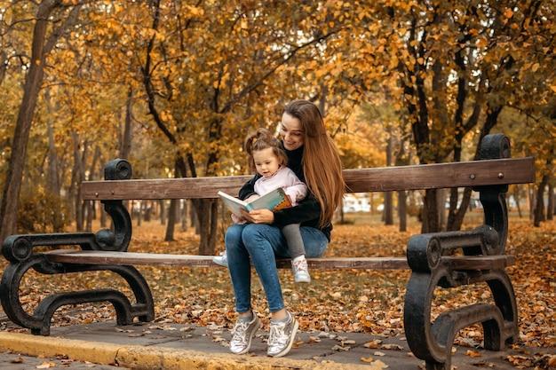 La giovane babysitter femminile e la neonata del bambino leggono il libro nella mamma felice della famiglia del parco autunnale e