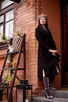 Giovane donna femminile appoggiata contro un muro di mattoni che indossa cappotto e cappello scuro Foto Premium