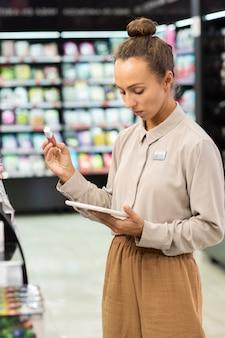 Giovane lavoratrice di un grande supermercato di bellezza contemporanea che confronta le informazioni nel touchpad con quelle del tubo di lucidalabbra