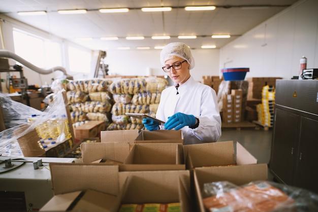 La giovane lavoratrice in abiti sterili sta usando la tavoletta per controllare il giusto numero di colli.