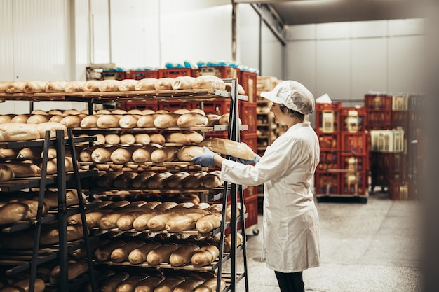 Giovane lavoratrice che lavora in panetteria. mette il pane sullo scaffale.