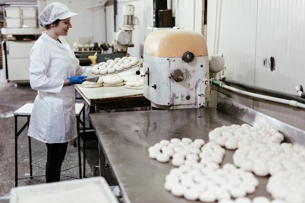 Giovane lavoratrice che lavora in una grande panetteria. preparazione del pane.