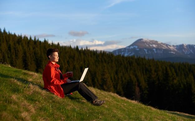Giovane femmina che lavora al suo computer portatile che riposa in cima alla montagna sul tramonto dopo l'escursione