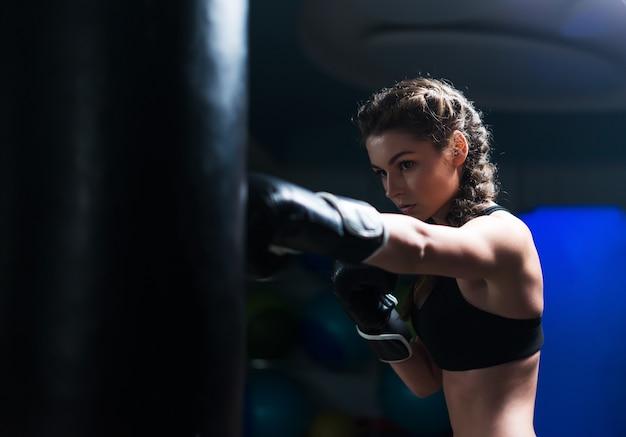 Giovane pugile combattente in forma ragazza che indossa guanti da boxe in allenamento con sacco da boxe pesante