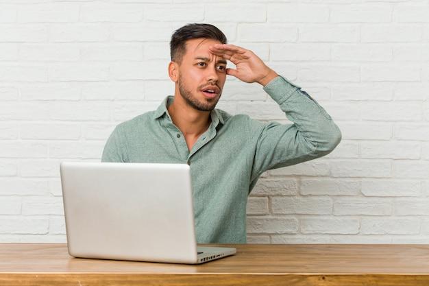 Giovane uomo filippino seduto a lavorare con il suo laptop guardando lontano tenendo la mano sulla fronte.